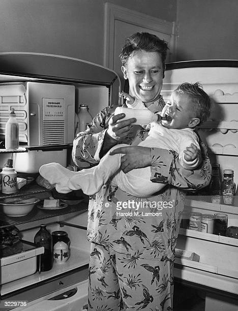 A father stands in front of an open refrigerator trying to feed a milk bottle to his crying baby 1940s The father wears pajamas with mallard ducks...