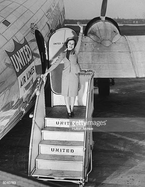 A female flight attendant standing on the stairway of a United Airlines airplane waving