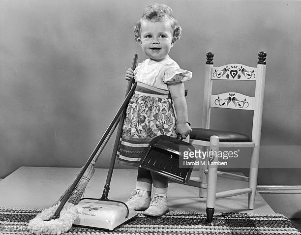 A female toddler smiles as she stands with a push sweeper a duster and a dust pan There is a small wooden chair and a rug