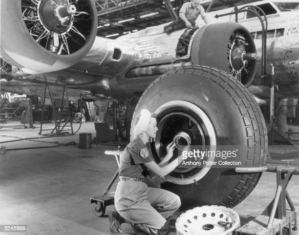 Female worker kneels while assembling the wheel of an airplane inside the Lockheed Aircraft Corporation factory, Burbank, California.