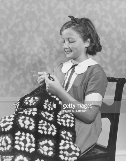 A girl in a collared dress sits in a chair crocheting a patterned blanket