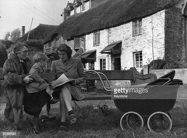 A grandmother mother and child enjoy the sunshine outside their cottage in Devon