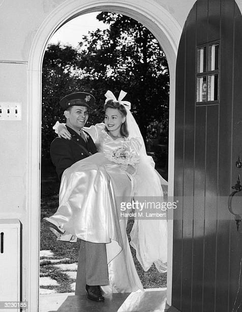 A groom wearing his military uniform carries his bride over the threshold of their home
