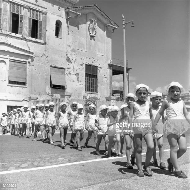 A group of children walking in line outside a convent in Rome where they are cared for Abandoned or orphaned during World War II the children are...