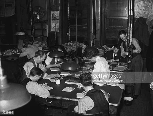 Group of journalists sit at desks and write on notepads inside the offices of the Minneapolis Journal newspaper. One of them loads a cannister into a...
