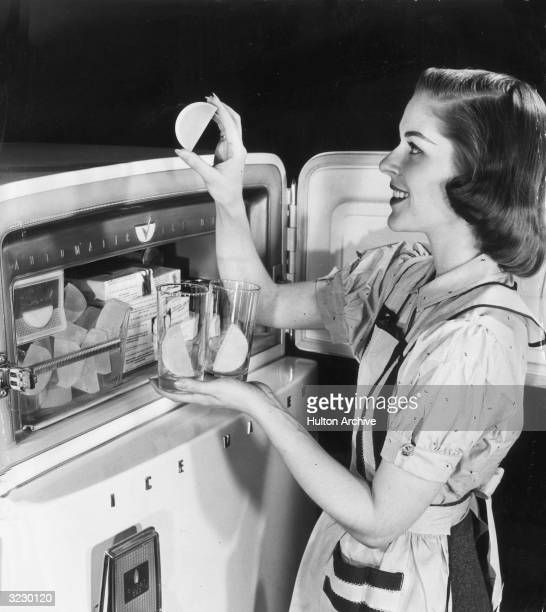 A housewife smiles as she stands at her freezer removing halfmoon shaped ice cubes from an automatic ice maker and putting them in glasses
