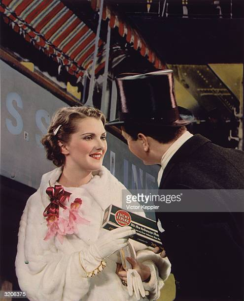 A man in a top hat and evening clothes hands a woman in a white fur coat and red corsage a carton of Lucky Strike cigarettes