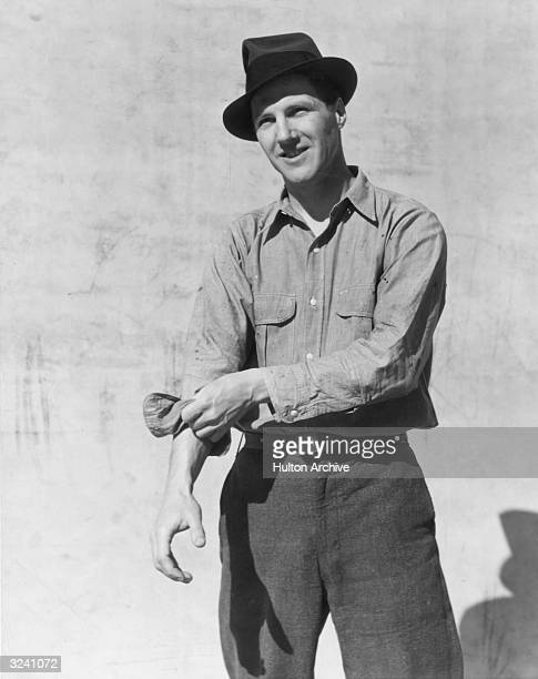 A man smiles as he stands in front of a wall rolling up one of his sleeves He wears a hat and wool pants