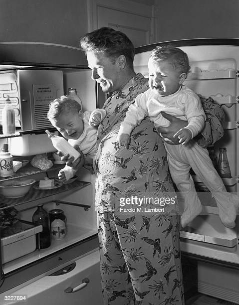 A man stands by an open refrigerator holding his twin crying babies and a bottle of milk He wears pyjamas