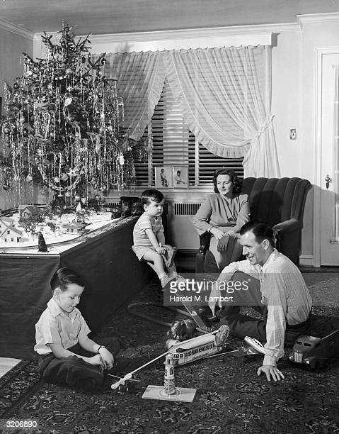 A mother and father watch their young sons playing with toys underneath a Christmas tree