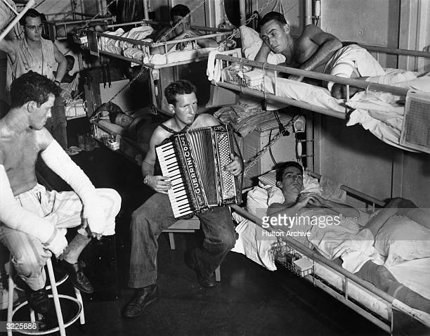 A Navy seaman sits and plays the accordion as other sailors listen while lying on their bunks One man sits on a wooden stool