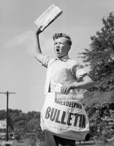 A newsboy carrying his bag yells while selling the 'Philadelphia Bulletin' newspaper outdoors on a street 1940s