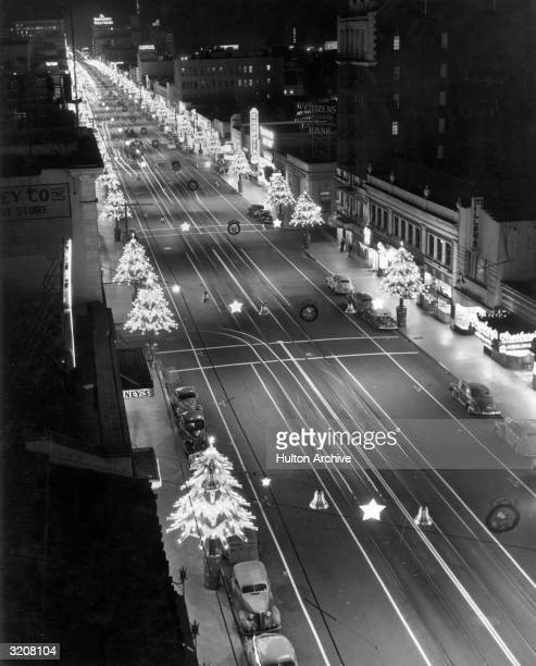 A nighttime view looking east down the 'Santa Claus Lane' portion of Hollywood Boulevard with illuminated Christmas tree decorations lining the...