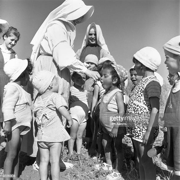 A nun feeding one of her charges at a convent in Rome where children who were abandoned or orphaned during World War II are cared for
