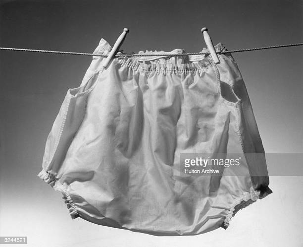 A pair of rubber baby diapers hang from a clothesline by wooden pins