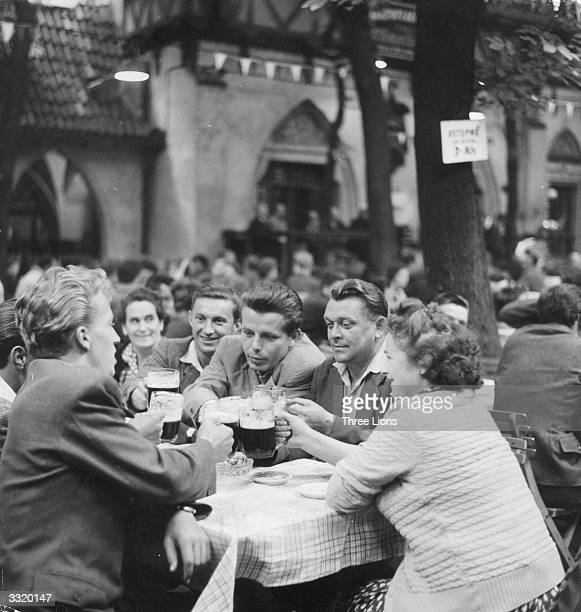 A party of beer drinkers at an outdoor restaurant in Prague Czechoslovakia