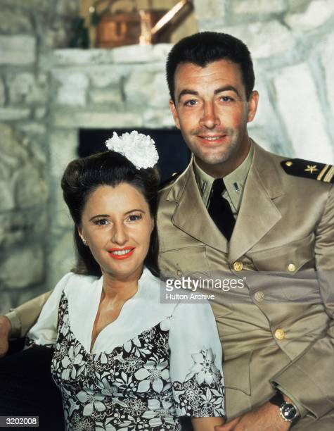 A portrait of American actor Barbara Stanwyck and her second husband actor Robert Taylor smiling while posing on a sofa Stanwyck wears a floral print...