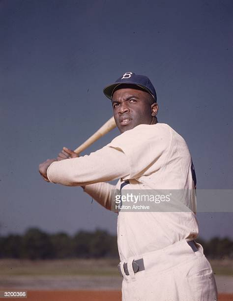Portrait of the Brooklyn Dodgers' Jackie Robinson in uniform, preparing to swing a baseball bat.