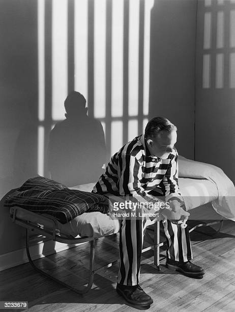 A prisoner in a striped prison uniform sits on a cot in a jail cell
