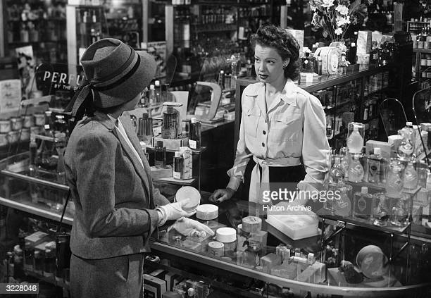 A saleswoman helping a customer choose a powder puff at a cosmetics counter in a department store 1940s Perfume bottle displays line the shelves