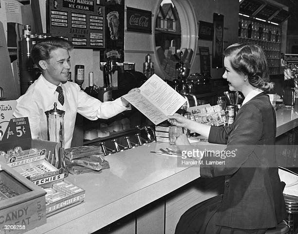 A smiling soda jerk hands a young woman a menu while she sits at the counter of an ice cream parlor