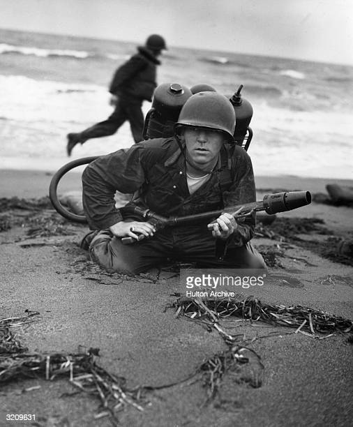 Soldier crouches low to the beach, holding a flame-thrower, wearing a backpack and helmet, during U.S. Marines amphibious training, Chigasaki, Japan.