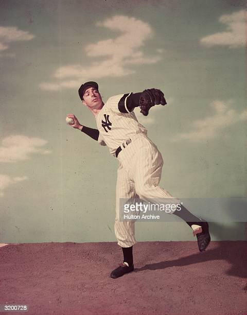 A studio portrait of the New York Yankees' Joe DiMaggio winding up for a pitch in front of a cloudy sky backdrop