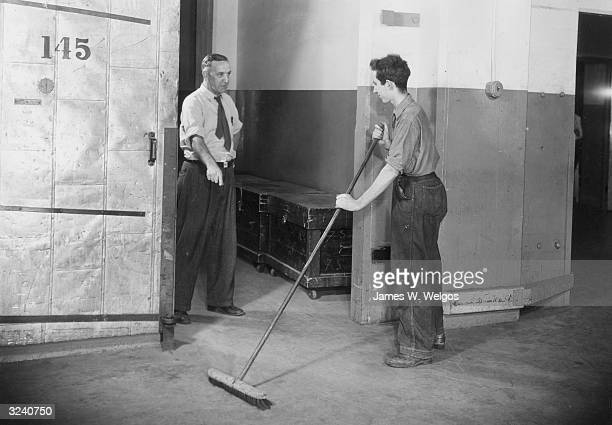 A supervisor points to the floor as he speaks to a young janitor sweeping a hallway with a push broom
