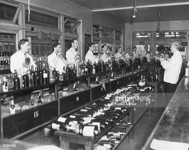 A teacher at a bartending school demonstrates the procedures for mixing alcoholic drinks to a row of male students in his class