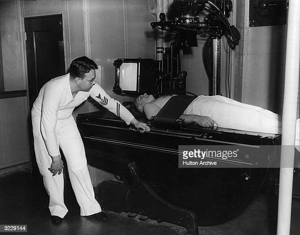 A U S Navy medical officer takes xrays of a patient laying on an adjustable General Electric xray table on board a U S Navy hospital ship The officer...