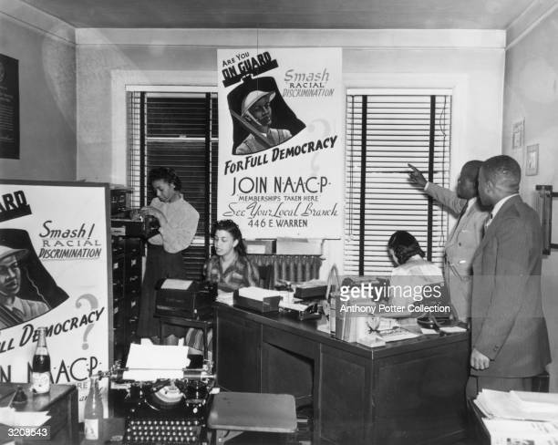 View inside an office of the National Association for the Advancement of Colored People , where a man points to a sign reading, 'Are You ON GUARD....