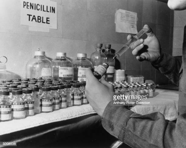 View of a man filling a syringe with penicillin in front of a counter filled with penicillin vials, 1940s.