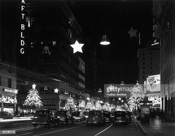 A view of Hollywood Boulevard at night with cars driving past illuminated Christmas decorations Los Angeles California
