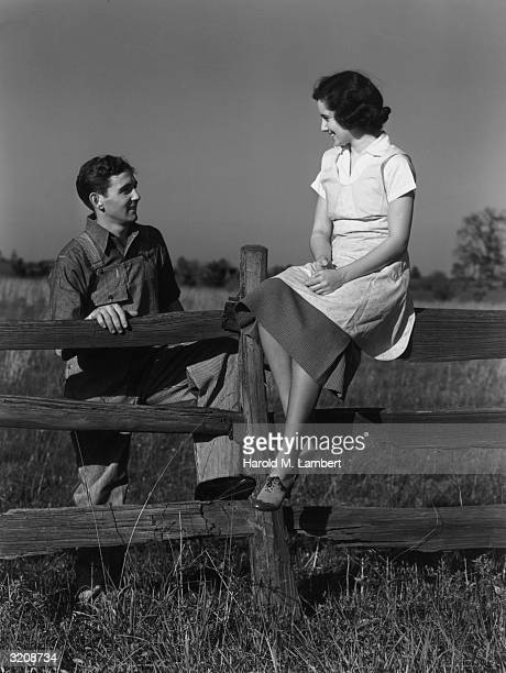 A woman in an apron and dress sits on top of a fence while talking to a man in overalls in an open field