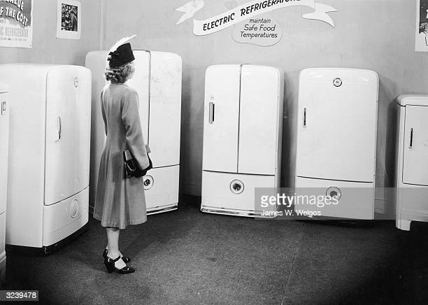 A woman looks at a display of electric refrigerators in an appliance store 1940s