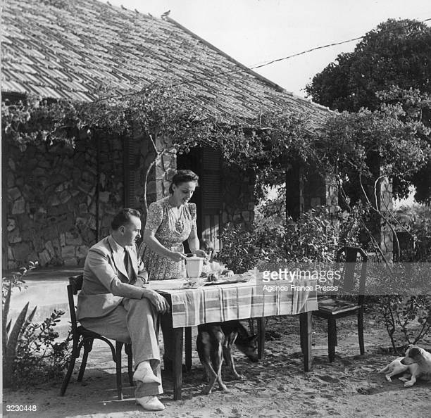 A woman serves tea to her husband and her daughter at a table in the backyard of their home in French west Africa A dog lays on the ground while...
