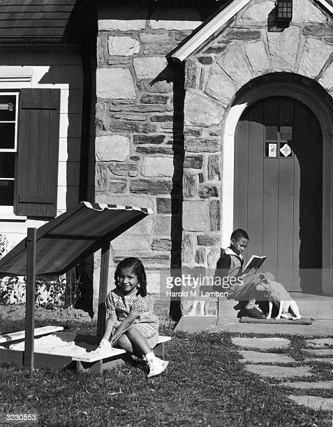 A young AfricanAmerican girl plays in a sandbox in front of her home while her brother reads a book on the front stoop with his pet dog at his feet