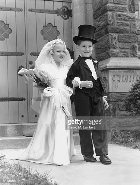 A young boy and a young girl stand arminarm in front of a church dressed as a bride and a groom The girl holds flowers The boy wears a top hat