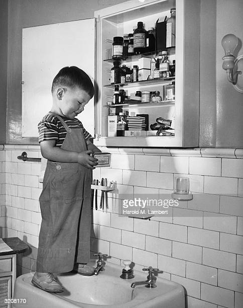 A young boy holds a box of poison while standing in front of a medicine cabinet on top of a sink in a bathroom 1940s