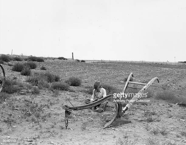 Young boy sits and plays in the dirt behind a wood-handled farm tiller in a farmer's field.