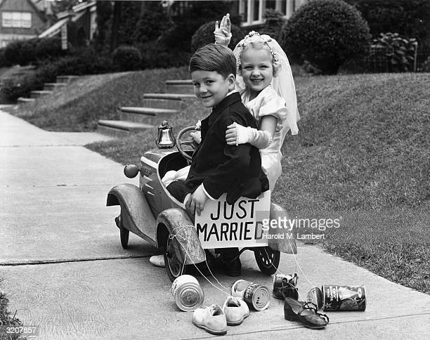 A young girl and a boy dressed as a bride and groom smile and wave while departing on a toy car which has a 'JUST MARRIED' sign and tins cans...