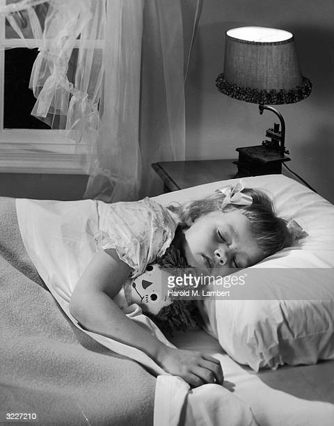 A young girl lies asleep in bed with a Raggedy Ann doll under her arm The light on her bedside table is lit