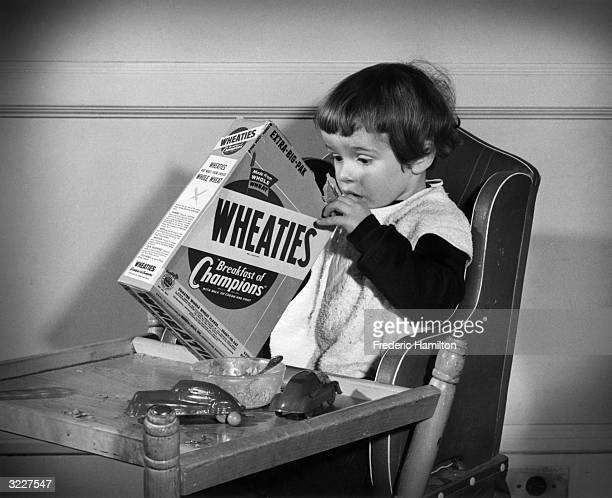 A young girl sits at a table digging with one hand in a box of Wheaties breakfast cereal There is an empty bowl and two toy cars on the table