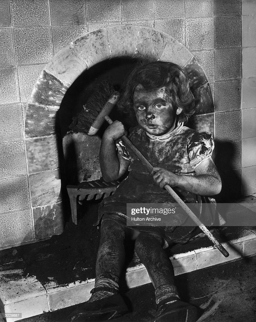 A Young Girl Sits By A Tile Fireplace Covered With Soot