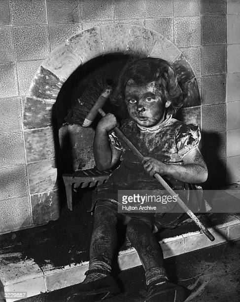 A young girl sits by a tile fireplace covered with soot holding a chimney brush