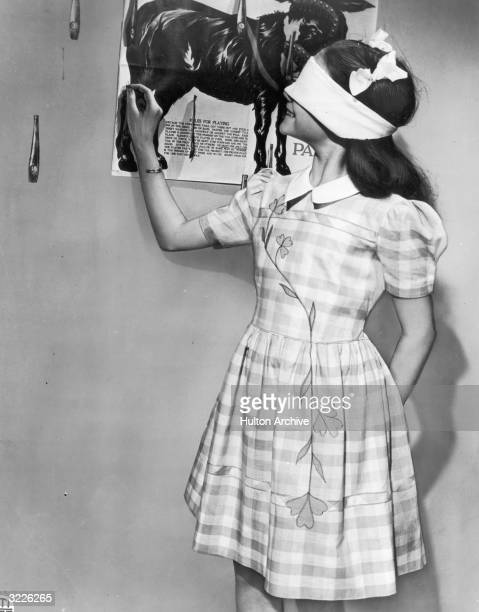 A young girl smiles while wearing a blindfold and pinning the leg of an illustrated donkey on the wall during a game of 'Pin the Tail on the Donkey'...