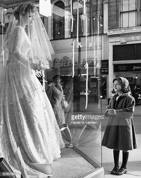 A young girl stands on the sidewalk outside of a department store window clasping her hands and smiling while looking up at a mannequin in a wedding...