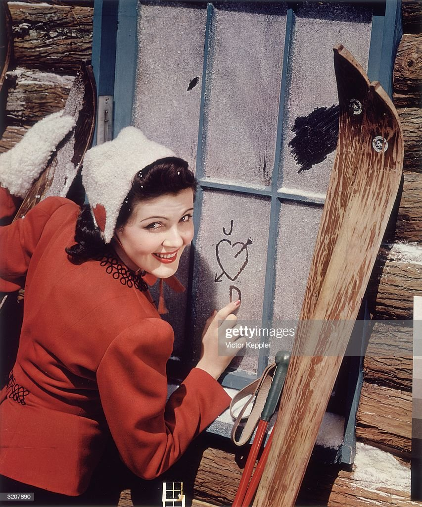 A young woman with skis stands at the frosted window of a cabin and draws a heart and the letters 'J' and 'D' in the frost. She wears a red coat and a white cap with a red heart stitched in the side.