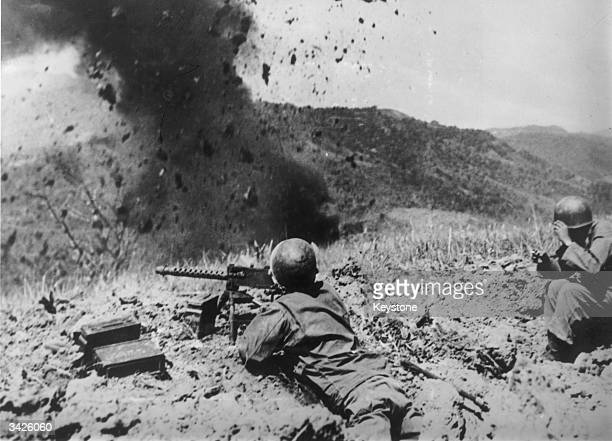 Advancing American forces using explosive charges to attack Japanese entrenched on the crest of a hill