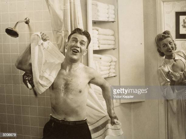 Advertisement shows a man singing next to a shower stall as he dries his back with a towel while a woman grins at him from the doorway